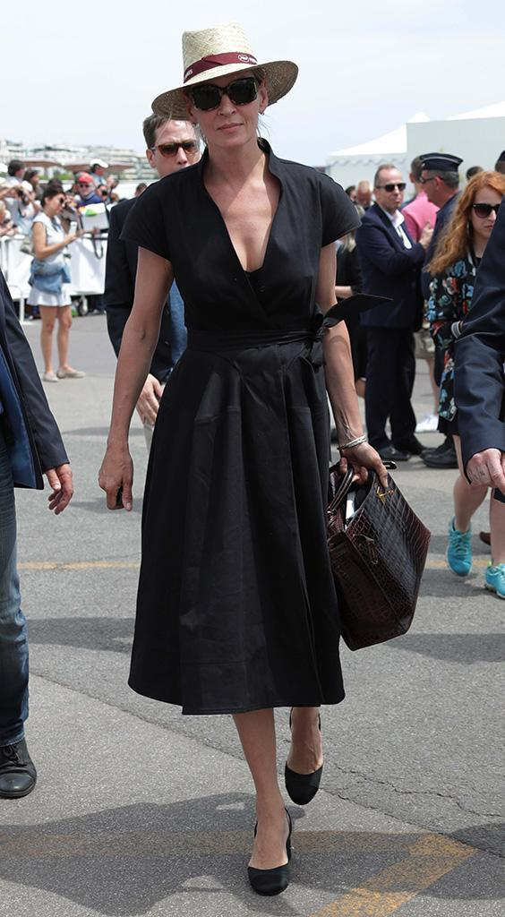 <p>In her low-cut, belted black frock, matching heels, and a straw hat, Uma fit right in with the posh crowd while walking around the resort city on the French Riviera on May 22. (Photo: Canio Romaniello/SilverHub/REX/Shutterstock)<br><br></p>