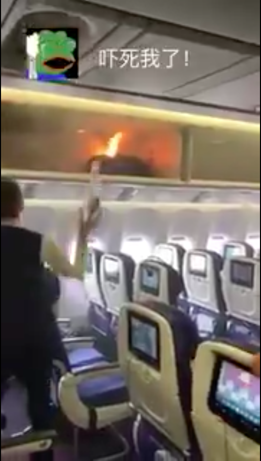 The cabin crew could be seen throwing water at the bag in an effort to extinguish it. Photo: Twitter