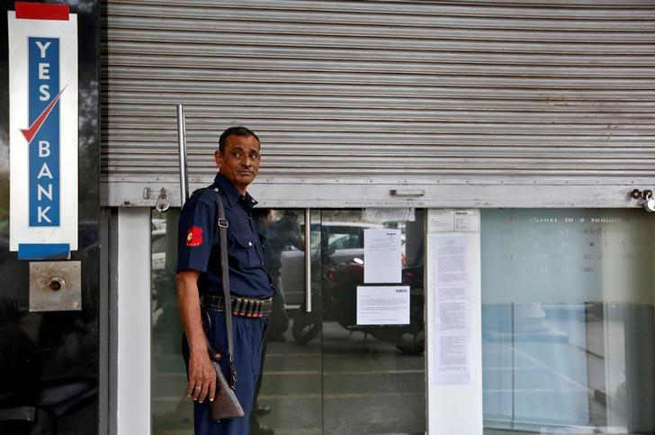 FILE PHOTO: A security guard stands outside a closed Yes Bank branch in New Delh