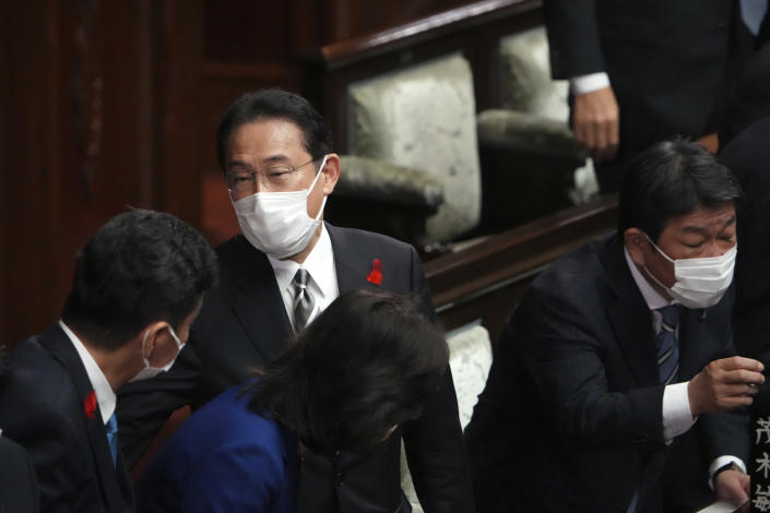 Japanese Prime Minister Fumio Kishida, center, and other lawmakers speak after dissolving the lower house, at an extraordinary Diet session at the lower house of parliament Thursday, Oct. 14, 2021, in Tokyo. Kishida dissolved the lower house of parliament Thursday, paving the way for Oct. 31 national elections.(AP Photo/Eugene Hoshiko)