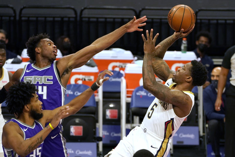 New Orleans Pelicans guard Eric Bledsoe, right, shoots against Sacramento Kings' Marvin Bagley III, left, and Buddy Hield, center, during the first quarter of an NBA basketball game in Sacramento, Calif., Sunday, Jan. 17, 2021. (AP Photo/Rich Pedroncelli)