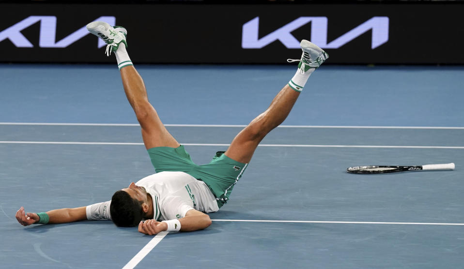 Serbia's Novak Djokovic falls as he celebrates after defeating Russia's Daniil Medvedev in the men's singles final at the Australian Open tennis championship in Melbourne, Australia, Sunday, Feb. 21, 2021.(AP Photo/Mark Dadswell)