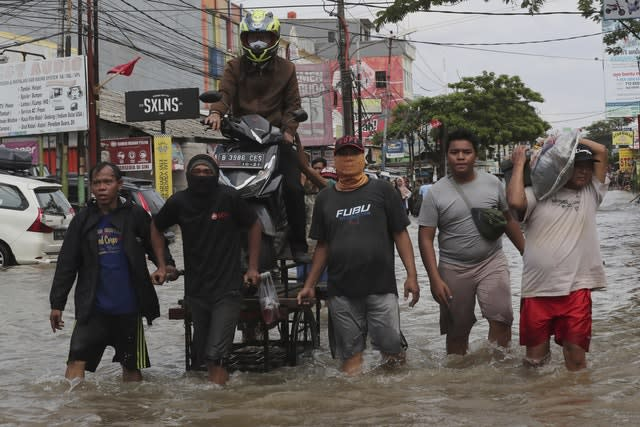 Indonesian men carry a motorbike with a cart through a flooded neighbourhood in Tanggerang on the outskirts of Jakarta, Indonesia