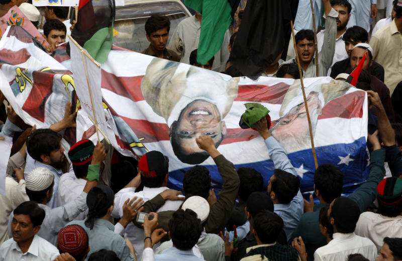 "Pakistani protesters hold a banner depicting U.S. President Barack Obama and pastor Terry Jones during a rally in Peshawar, Pakistan as a part of widespread anger across the Muslim world about a film ridiculing Islam's Prophet Muhammad, on Thursday, Sept. 20, 2012. Recent images of angry mobs in Arab cities burning American flags and attacking U.S. diplomatic posts suggest the Muslim world is no less enraged at the United States than when President George W. Bush had to duck shoes hurled at him in Baghdad. But more than three years after Obama declared in Cairo that he would seek ""a new beginning"" in U.S.-Muslim relations, a closer look reveals strides as well as setbacks. (AP Photo/Mohammad Sajjad)"