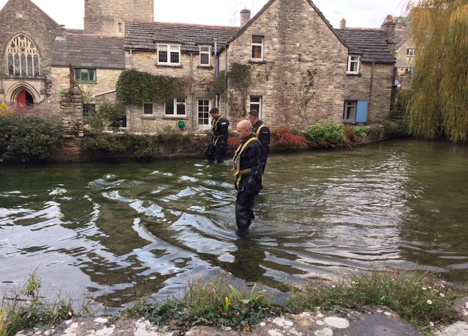A police team searches a mill pond in Swanage (PA Images)