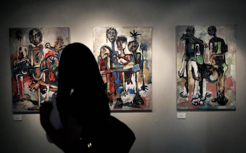 "In this photo taken Saturday, May 10, 2014, a woman looks at a series of three acrylic on canvas paintings named Hamamah, by Palestinian artist Ismail Dahlan, during an art exhibition ""Traces, a testimony to memory,"" displaying over forty Palestinian artists work from Gaza, in the West Bank city of Ramallah. Fifty-three paintings and two sculptures by 45 artists have gone on display in the West Bank city of Ramallah, said Haneen Qatamesh, a spokeswoman for one of the sponsors, the Palestinian company PADICO. Since Saturday's opening, 12 works have been sold for prices ranging from $850 to $9,000, she said. (AP Photo/Nasser Nasser)"