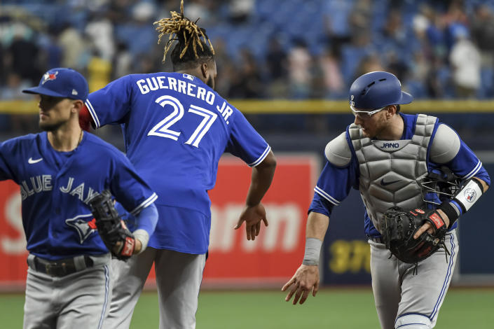 Toronto Blue Jays' Vladimir Guerrero Jr. (27) and Danny Jansen celebrate a win over the Tampa Bay Rays during a baseball game Sunday, July 11, 2021, in St. Petersburg, Fla.(AP Photo/Steve Nesius)