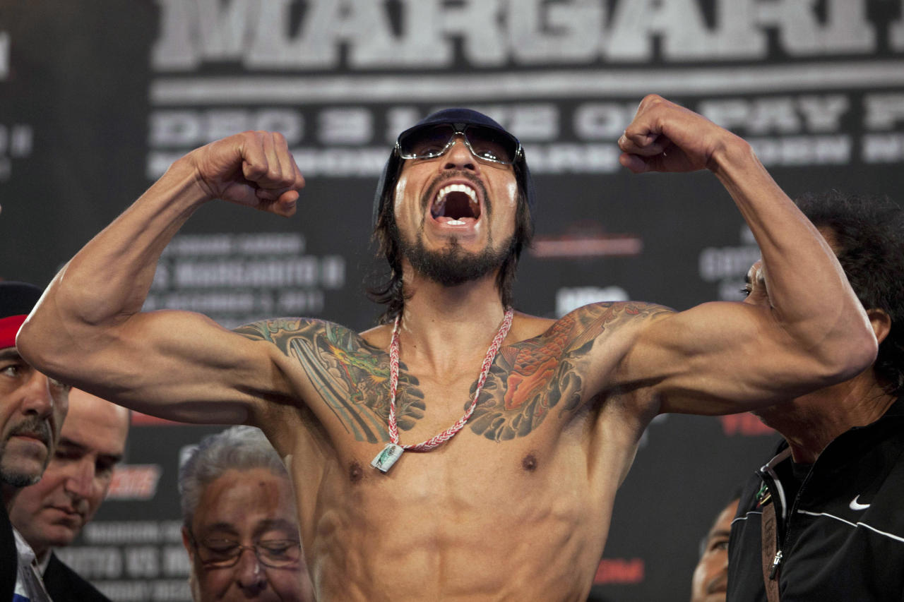 Antonio Margarito of Mexico flexes his muscles while standing on the scale during the official weigh-in for his WBA world junior middleweight title fight against Miguel Cotto of Puerto Rico at Madison Square Garden in New York December 2, 2011. The fight will take place on Saturday. (REUTERS/Andrew Burton)