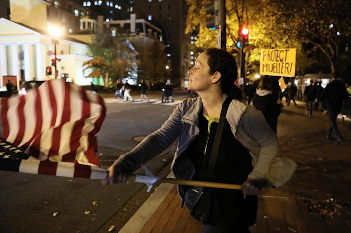 <p>A woman waves a U.S. flag at passing cars as protesters rally to demand the U.S. government protect the investigation led by special counsel Robert Mueller into alleged Russian meddling in the 2016 Trump campaign, outside the White House, in Washington, D.C., Nov. 8, 2018. (Photo: Jonathan Ernst/Reuters) </p>
