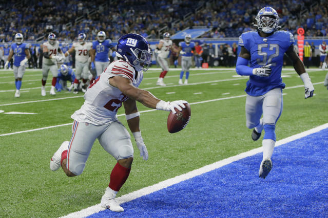 New York Giants running back Saquon Barkley (26) runs ahead of Detroit Lions outside linebacker Christian Jones (52) and scores during the second half of an NFL football game, Sunday, Oct. 27, 2019, in Detroit. (AP Photo/Duane Burleson)