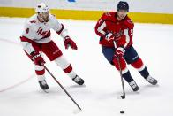 Washington Capitals center Evgeny Kuznetsov (92), from Russia, passes the puck as Carolina Hurricanes defenseman Joel Edmundson (6), Canada, defends during the first period of an NHL hockey game Monday, Jan. 13, 2020, in Washington. (AP Photo/Al Drago)