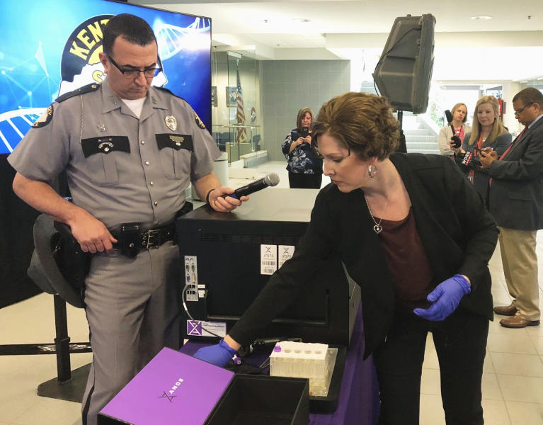 FILE - In this April 10, 2019, file photo, Regina Wells, foreground right, a forensic laboratories supervisor with the Kentucky State Police, demonstrates new crime-fighting technology in Frankfort, Ky. Rapid DNA machines roughly the size of an office printer have helped solve rape cases in Kentucky. Now a state board in Texas has asked a growing government provider of the DNA equipment used in those high-profile projects to halt work amid concerns of potentially jeopardized criminal cases, according to a letter obtained by The Associated Press. (AP Photo/Bruce Schreiner, File)