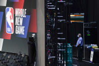 FILE - In this July 29, 2020, file photo, a security guard wearing a face mask stands near a basketball arena inside thre NBA bubble at ESPN Wide World of Sports Complex in Lake Buena Vista, Fla. The NBA had teams in the bubble for three months. The NHL playoff bubble lasted 65 days from the time teams arrived in Toronto and Edmonton, Alberta, until Tampa Bay won the Stanley Cup. Officials from both leagues beamed that mask, distancing and other protocols were still being followed strictly on the final day. (AP Photo/Ashley Landis, File)