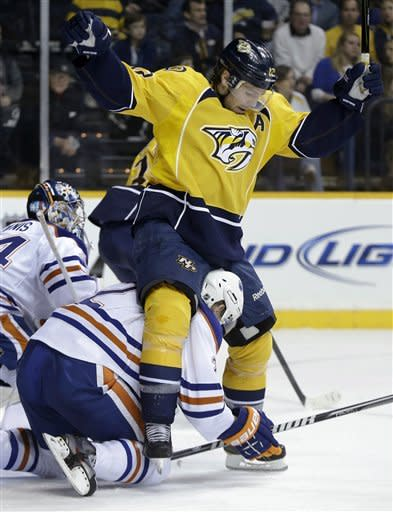 Nashville Predators center Mike Fisher, top, gets tangled with Edmonton Oilers defenseman Jeff Petry during the second period of an NHL hockey game Friday, March 8, 2013, in Nashville, Tenn. (AP Photo/Mark Humphrey)