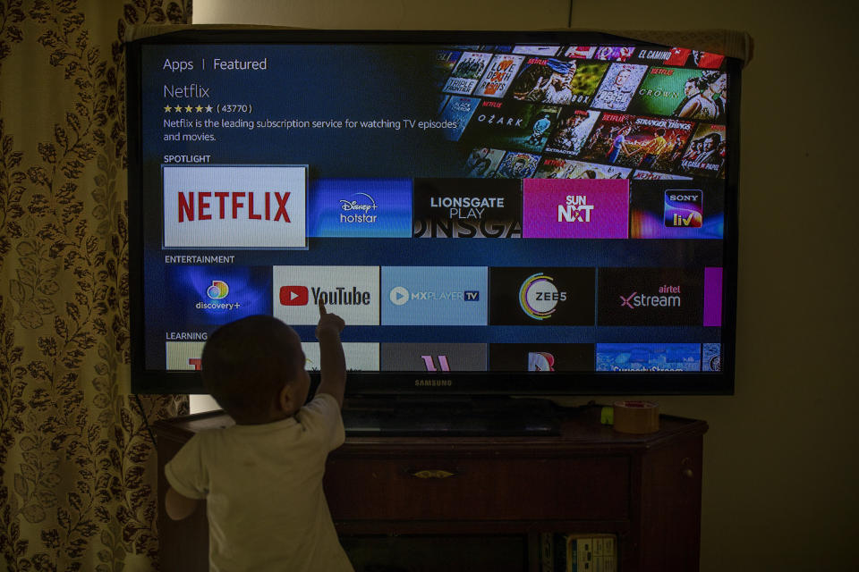 A child touches a TV screen displaying OTT streaming apps at his home in New Delhi, India, Thursday, Feb. 25, 2021. India has rolled out new regulations for social media companies and digital streaming websites to make them more accountable for the online content shared on their platforms. (AP Photo/Altaf Qadri)