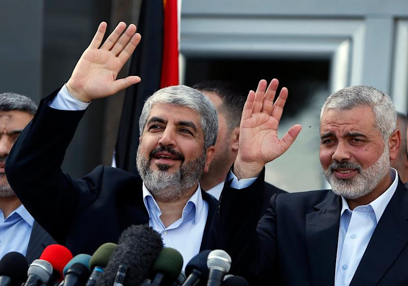In this Dec. 7, 2012 file photo, formerly exiled Hamas chief Khaled Mashaal, left, and Gaza's Hamas Prime Minister Ismail Haniyeh wave during a news conference upon Mashaal's arrival at the Rafah crossing in the southern Gaza Strip - AP