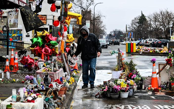 A man removes dead flowers from the makeshift memorial of George Floyd - Chandan Khanna/AFP