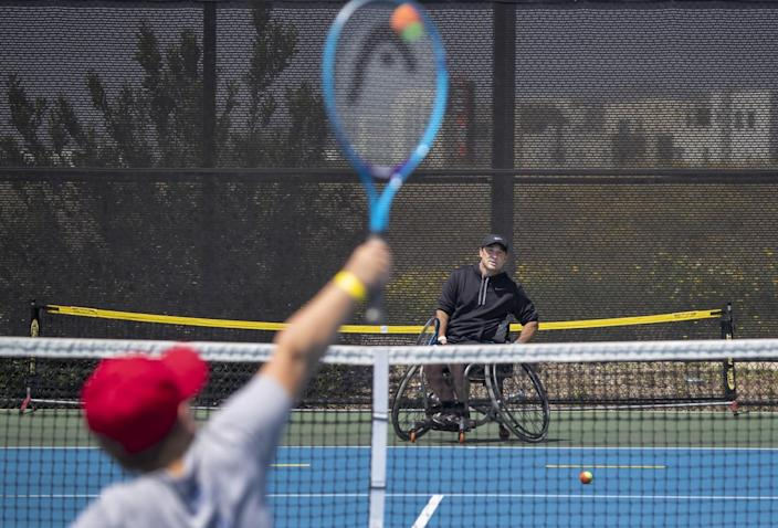 A youth player hits the ball to Paralympian David Wagner during a clinic in Irvine.