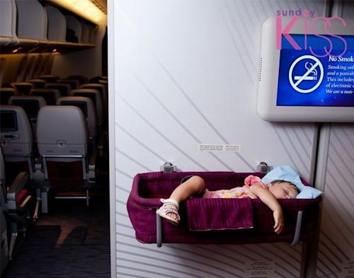 Travel with children. Small two year old baby girl sleep in a special bassinet on a airplane
