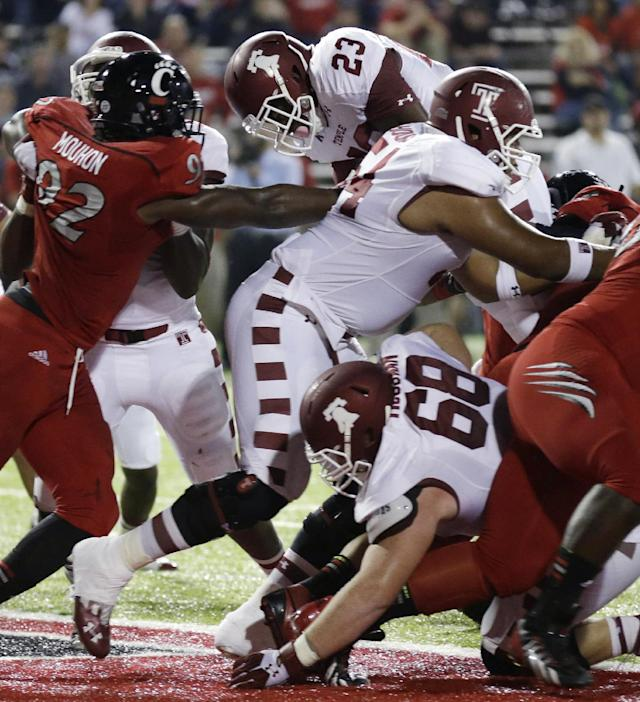 Temple running back Zaire Williams (23) jumps over the goal line for a 1-yard touchdown run in the first half of an NCAA college football game, against Cincinnati defender Silverberry Mouhon (92), Friday, Oct. 11, 2013, in Cincinnati. Brendan McGowan (68) and Zach Hooks (54) block. (AP Photo/Al Behrman)