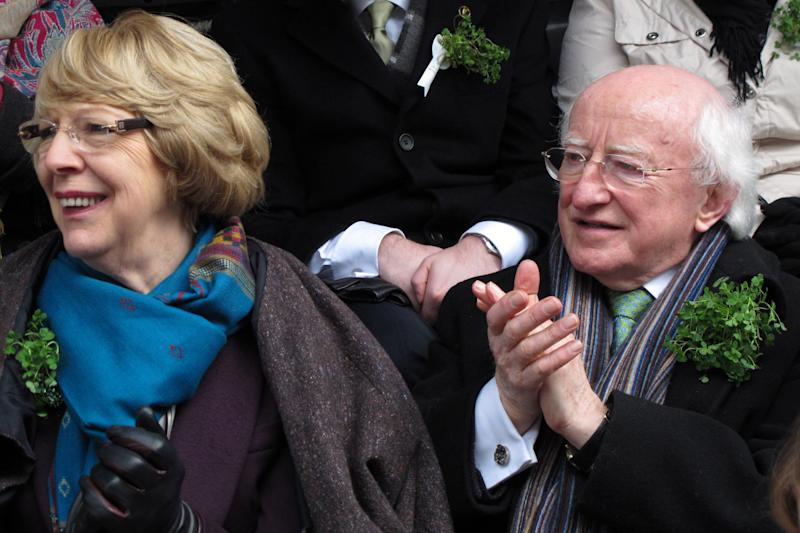 CAPTION CORRECTION, CORRECTS NAME OF WIFE - Ireland's President Michael D. Higgins, right, and his wife Sabina don sprigs of shamrock as they applaud passing groups at the St. Patrick's Day parade, Dublin, Sunday, March 17, 2013. Never mind the fickle Irish weather. A chilly, damp Dublin celebrated St. Patrick's Day with artistic flair Sunday as the focal point for a weekend of Irish celebrations worldwide. (AP Photo/Shawn Pogatchnik)