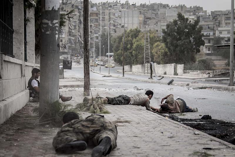 In this Saturday, Oct. 20, 2012 photo, Free Syrian Army fighters crawl on the sidewalk as they attempt to rescue a Syrian civilian who was shot twice, in his stomach and his back, by a Syrian army sniper while was walking on the frontline in the Bustan al-Qasr neighborhood of Aleppo, Syria. (AP Photo/Narciso Contreras)