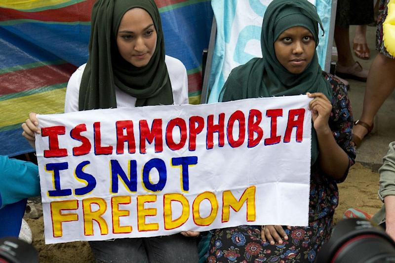 Two women hold a sign at an anti-Islamophobia protest: Getty