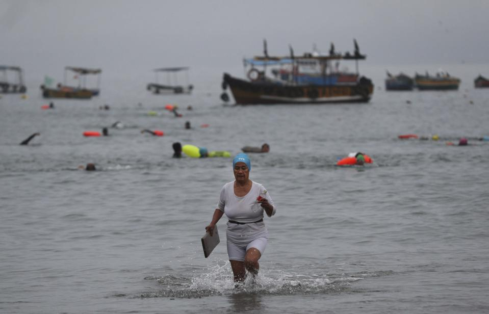 An open water swimmer exits the sea on Pescadores beach, where swimming in the ocean is booming while pools are closed due to the COVID-19 pandemic in Lima, Peru, early Tuesday, April 27, 2021. One of the few sporting disciplines that have been maintained during the coronavirus pandemic is swimming, which due to the closure of the swimming pools, has moved to the open sea. (AP Photo/Martin Mejia)