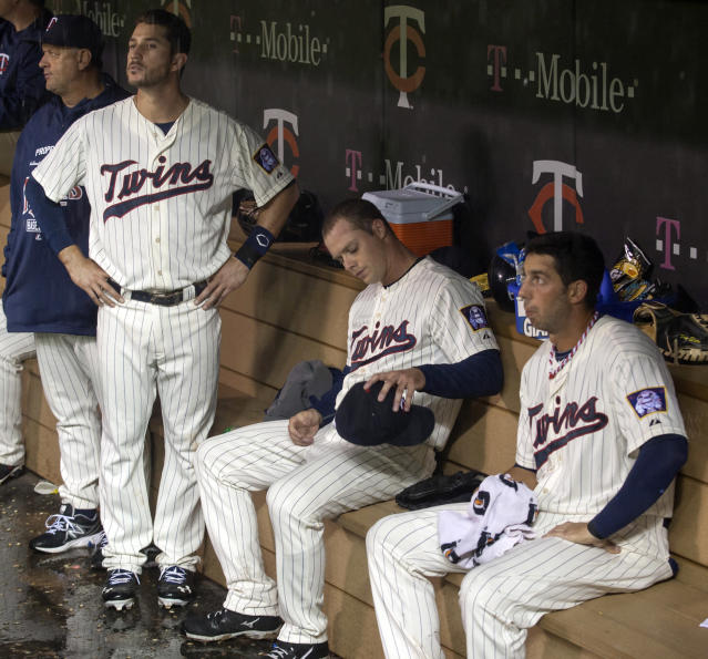 Minnesota Twins starting pitcher Andrew Albers, center, sits in the dugout with teammates Trevor Plouffe, left, and Chris Colabello, right, during a fourth inning rain delay of a baseball game against the Tampa Bay Rays, Saturday, Sept. 14, 2013, in Minneapolis. (AP Photo/Paul Battaglia)
