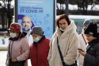 """A group of people some of them wearing face masks walk past the poster showing a portrait of Dr. Denis Protsenko and words reading """"Get vaccinated against covid-19!!"""" Near a vaccination point at VDNKh, The Exhibition of Achievements of National Economy in Moscow, Russia, Friday, April 2, 2021. Moscow is one of the few places in the world where one can get vaccinated against COVID-19 within hours of deciding to do so. To boost the demand, officials in Moscow this week started offering 1,000-ruble ($13) coupons to people over 60 for getting vaccinated. (AP Photo/Alexander Zemlianichenko)"""