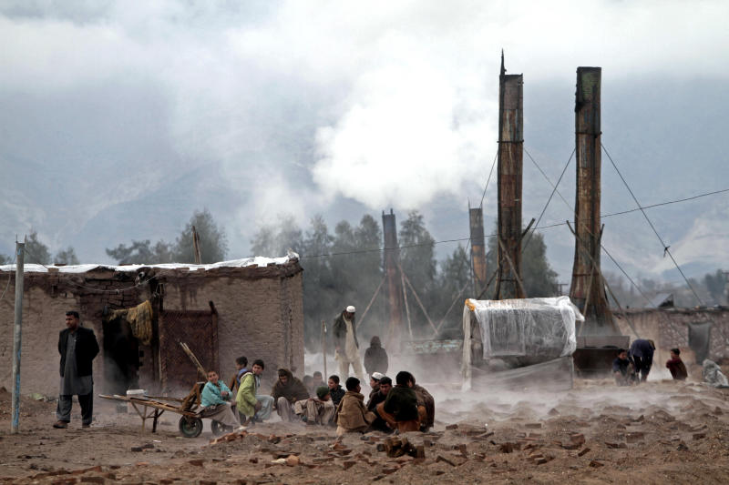 Afghan boys warm their hands over a brick factory fire during a cold day in the outskirt of Jalalabad east of Kabul, Afghanistan, Monday, Feb. 04, 2013. Kabul has been experiencing below freezing weather and snow for several days. (AP Photo/Rahmat Gul)