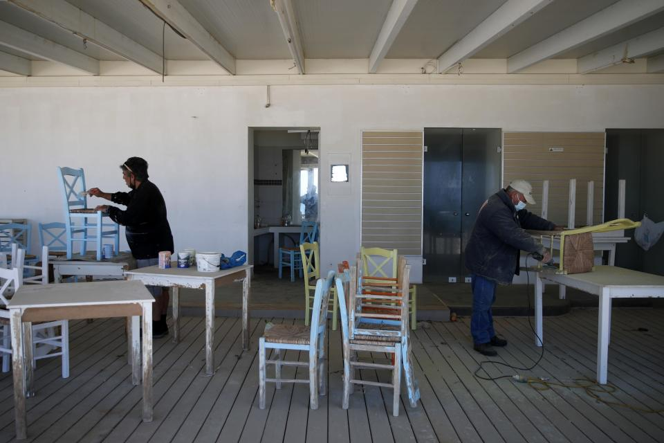 Workers paint the chairs of a tavern in Chora, on the Aegean island of Naxos, Greece, Tuesday, May 11, 2021. With debts piling up, southern European countries are racing to reopen their tourism services despite delays in rolling out a planned EU-wide travel pass. Greece Friday became the latest country to open up its vacation season as it dismantles lockdown restrictions and focuses its vaccination program on the islands. (AP Photo/Thanassis Stavrakis)