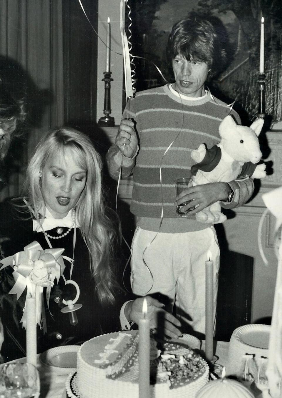 <p>Mick Jagger held a balloon and stuffed animal, while Jerry Hall prepared to share the cake at her baby shower.</p>