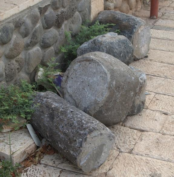 Roman column fragments, along with the top of a rotary quern (for grinding), lying on the side of a road in the modern-day town of Migdal and believed to be part of a newfound ancient town.