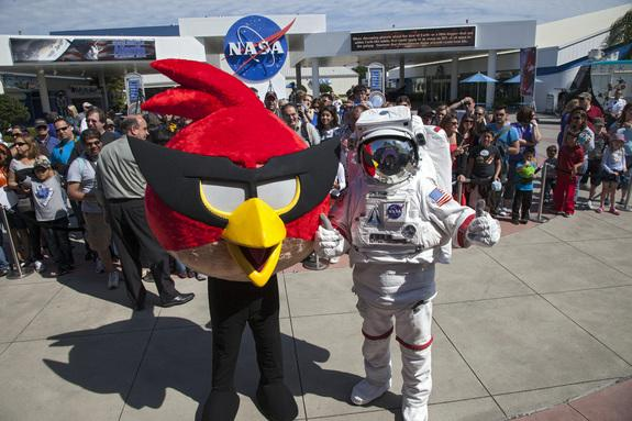 At NASA's Kennedy Space Center Visitor Complex in Florida, the Spaceperson and Red Bird, one of the Angry Bird characters, welcome visitors to the Angry Birds Space Encounter grand opening ceremony. Image was released March 22, 2013.