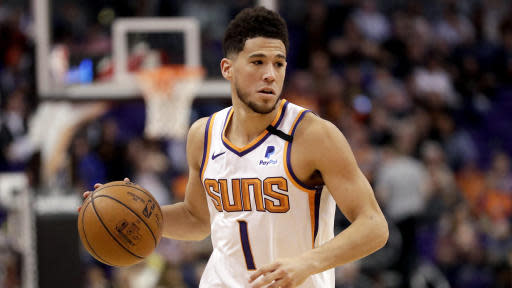 Phoenix Suns guard Devin Booker (1) looks to pass against the Golden State Warriors during the second half of an NBA basketball game, Wednesday, Feb. 12, 2020, in Phoenix. (AP Photo/Matt York)