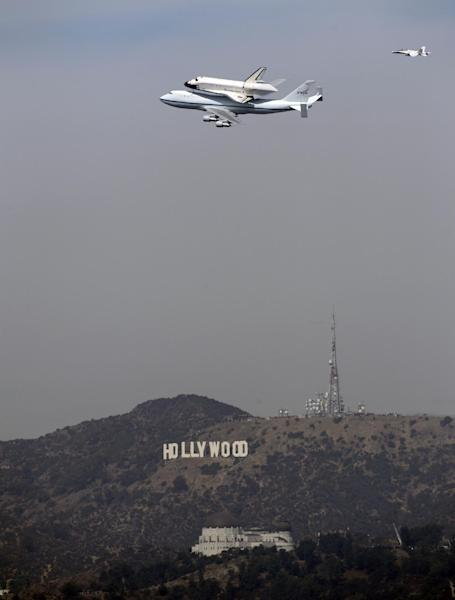 The Space Shuttle Endeavour atop a modified 747 passes the Hollywood Sign and the Griffith Observatory as seen from Dodger Stadium, Friday, Sept. 21, 2012, in Los Angeles. Endeavour will be permanently displayed at the California Science Center in Los Angeles. (AP Photo/Mark J. Terrill)