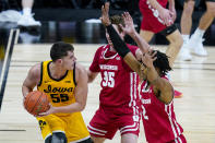 Iowa center Luka Garza (55) gets trapped on the baseline by Wisconsin forwards Nate Reuvers (35) and Aleem Ford (2) during the second half of an NCAA college basketball game at the Big Ten Conference men's tournament in Indianapolis, Friday, March 12, 2021. (AP Photo/Michael Conroy)