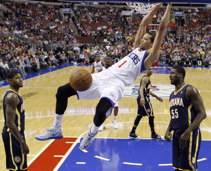 Philadelphia 76ers' Michael Carter-Williams, center, hangs on the rim after a dunk as Indiana Pacers' Paul George, left, and Roy Hibbert look on during the first half of an NBA basketball game on Friday, March 14, 2014, in Philadelphia. (AP Photo/Matt Slocum)