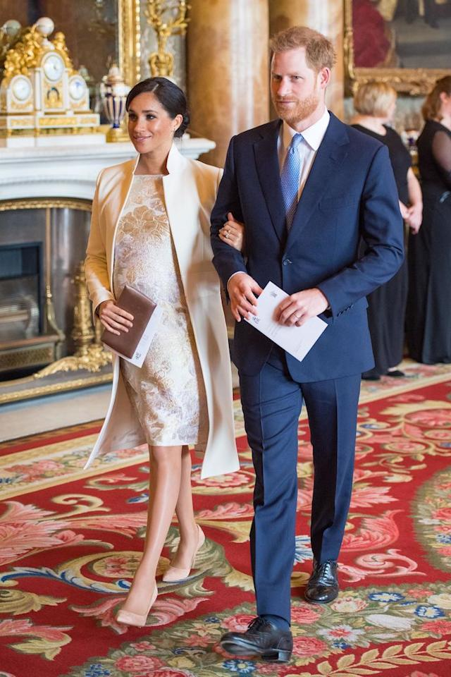 <p>To mark Charles' 50th anniversary as the Prince of Wales, Meghan donned her Amanda Wakeley 'Crombie' coat with a floral brocade dress, her Wilbur and Gussie Oyster Clutch and her Paul Andrews pumps. <em>[Photo: Getty]</em> </p>