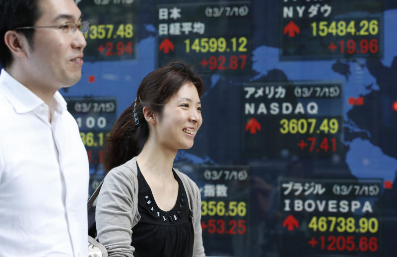 People walk by an electronic stock board in Tokyo, Tuesday, July 16, 2013. Weaker-than-expected U.S. retail sales sent most Asian stock markets lower Tuesday as investors awaited congressional testimony from Federal Reserve chairman Ben Bernanke later in the week.(AP Photo/Shizuo Kambayashi)