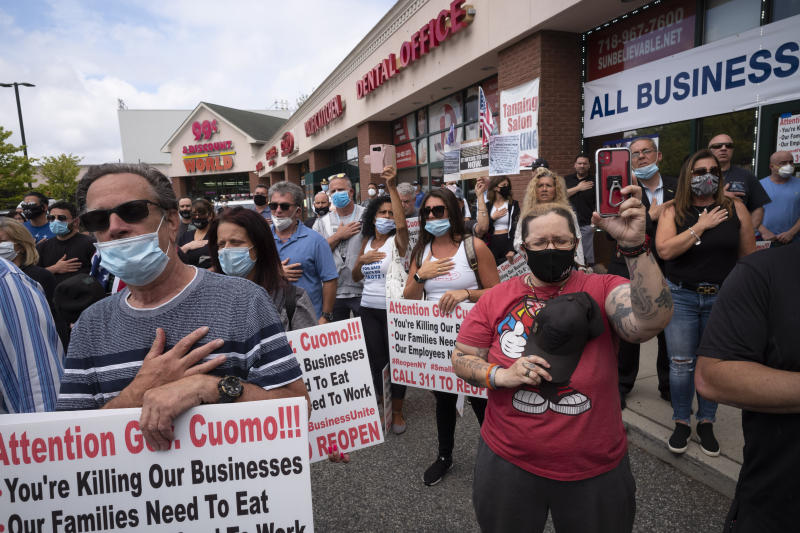 A crowd gives the Pledge of Allegiance while supporting Bobby Catone, the owner of a Staten Island tanning salon, Thursday, May 28, 2020, in New York. Catone opened the salon briefly Thursday morning in defiance of a law requiring non-essential businesses to remain closed during the coronavirus pandemic. (AP Photo/Mark Lennihan)