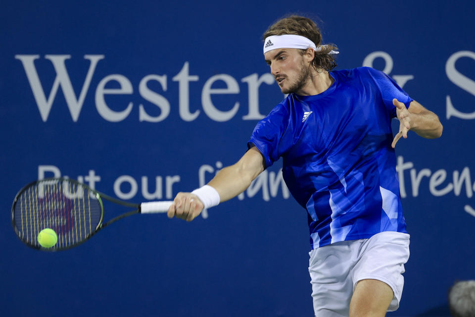 Stefanos Tsitsipas, of Greece, returns to Felix Auger-Aliassime, of Canada, during the Western & Southern Open tennis tournament Friday, Aug. 20, 2021, in Mason, Ohio. (AP Photo/Aaron Doster)
