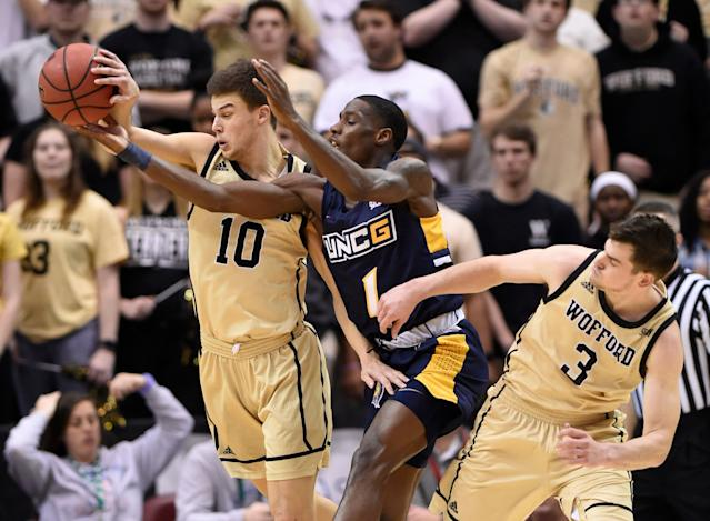 Wofford guard Nathan Hoover (10), UNC-Greensboro guard Isaiah Miller (1) and Wofford guard Fletcher Magee (3) scramble for the ball in the first half of an NCAA college basketball game for the Southern Conference tournament championship, Monday, March 11, 2019, in Asheville, N.C. (AP Photo/Kathy Kmonicek)