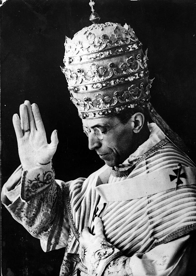 December 1939:  Pope Pius XII (1876 - 1958), Eugenio Pacelli, bestowing a blessing during a visit to the King and Queen of Italy in Rome, wearing his papal mitre.  (Photo by Keystone/Getty Images)