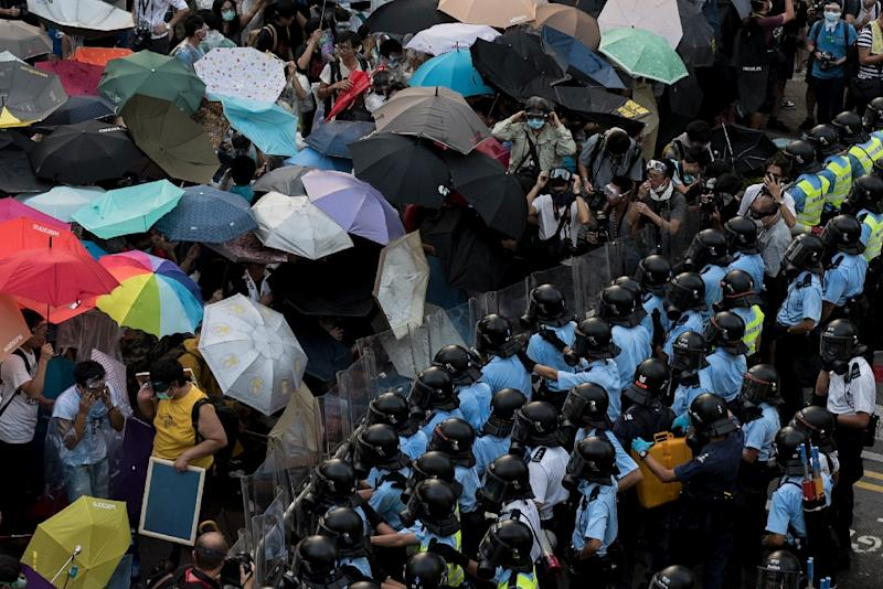 The Occupy trio urged people to join what became known as the Umbrella Movement as protesters used umbrellas to shield themselves from tear gas and pepper spray (AFP Photo/Alex Ogle)