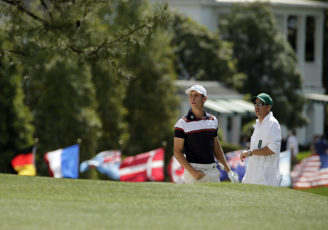 Oliver Goss, of Australia, and his caddie Brian Tam look for Goss' ball after hitting out of a bunker on the first fairway during the fourth round of the Masters golf tournament Sunday, April 13, 2014, in Augusta, Ga. (AP Photo/Charlie Riedel)