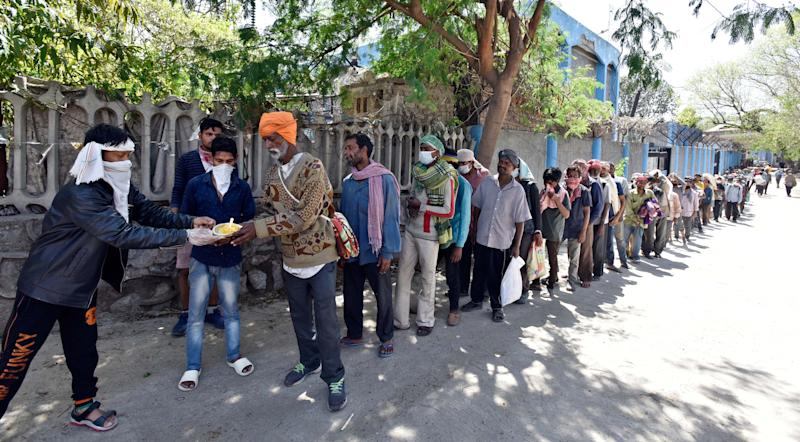 NEW DELHI, INDIA - MARCH 30: Homeless people stand in a queue to collect food on Day 6 of the 21 day nationwide lockdown imposed by PM Narendra Modi to curb the spread of coronavirus, at Yamuna Ghat, near ISBT, on March 30, 2020 in New Delhi, India. (Photo by Sanjeev Verma/Hindustan Times via Getty Images)