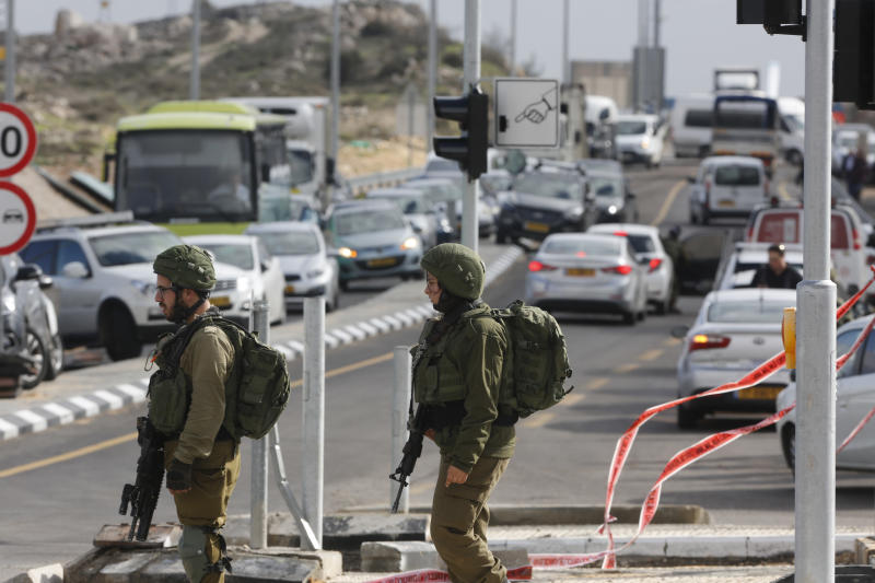 Israeli soldiers stand at the scene of an attack near the settlement of Givat Assaf in the West Bank, Thursday, Dec. 13, 2018. A Palestinian gunman opened fire at a bus stop outside a West Bank settlement on Thursday, shooting at soldiers and civilians and killing at least two Israelis before fleeing, the military and Israel's rescue service said. (AP Photo/Nasser Shiyoukhi)