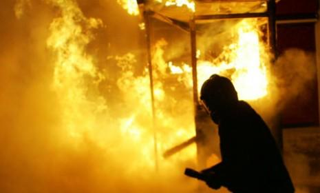 A fireman tries to extinguish a fire as protesters clash with police outside the parliament buildings in Athens. Greeks tried unsuccessfully to stop the government from approving more budget cuts.